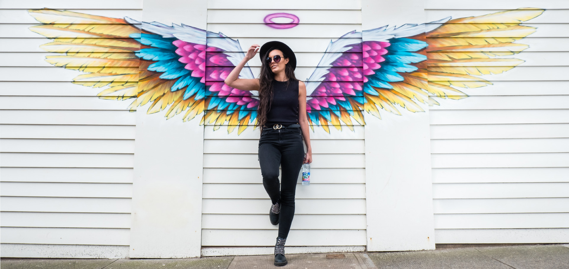 Mac-b photoshoot, a woman holding a bottle in front of a wing graphic on a wall