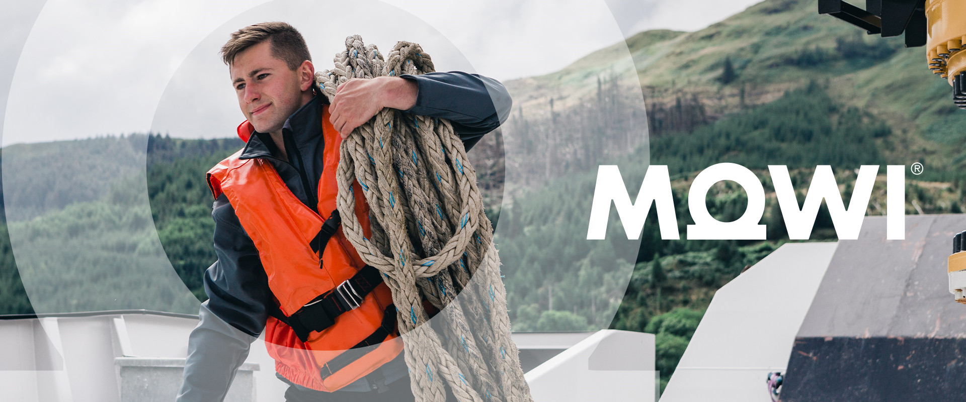 A man wearing a Mowi lifejacket on a boat, hauling some rope on his shoulder and the Scottish Highlands behind